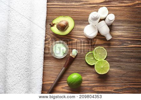 Composition with cosmetic mask, avocado and slices of lime on wooden background