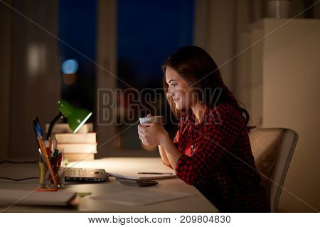 education, technology, freelance, overwork and people concept - woman or student girl with laptop computer drinking coffee at night home