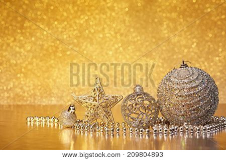 Christmas decoration with silver balls, star and garlands lying on a golden background. New year and Christmas background with copy space for text. Greeting card.