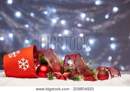 Christmas decoration with red bucket, fir branches, red balls and star lying on snow on a grey background with lightes of garland. New year and Christmas background with copy space for text.
