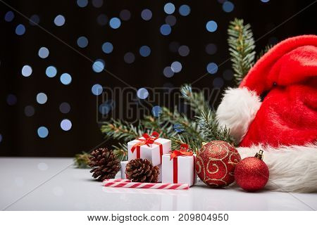 Santa claus hat, fir tree branch with decoration, gift boxes  on a black background with lightes of garland.  New year and Christmas background with copy space for text. Greeting card.