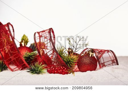 Christmas decoration with red tape, fir branches, red balls  lying on snow on aon a white background. New year and Christmas background with copy space for text. Greeting card.