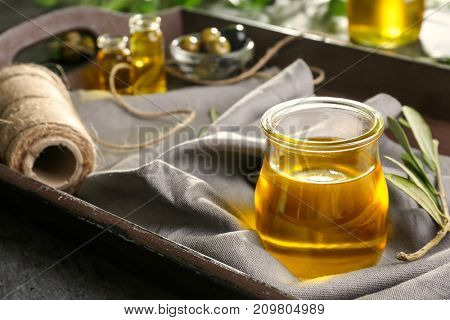 Jar with olive oil on tray