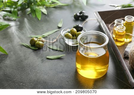 Jar with olive oil on grunge table