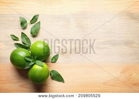 Composition with lime and mint on wooden background
