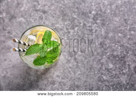 Glass of cocktail with mint and lemon on table