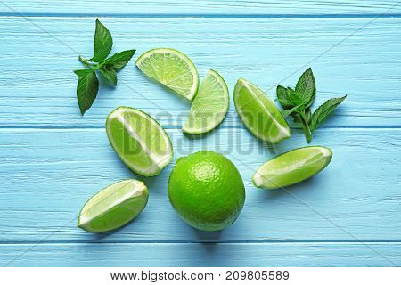 Composition with lime and mint on color wooden background
