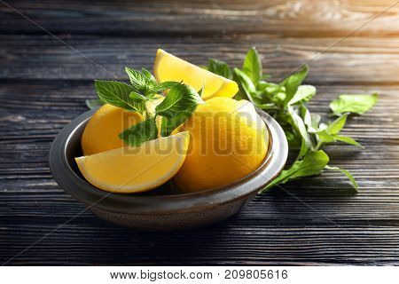 Bowl with lemon and mint on wooden background