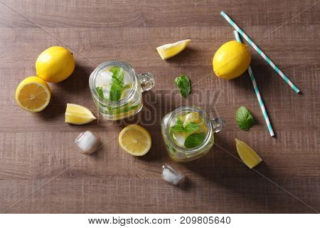Mason jars with mojito cocktail on wooden background