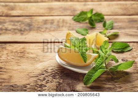 Plate with mint and lemon on wooden background