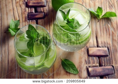 Glasses of cocktail with mint and lime on wooden board