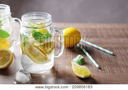 Mason jar with mojito cocktail on wooden table
