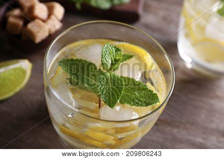 Glass of cocktail with lemon and mint on wooden table