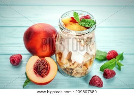 Jar with oat flakes and fresh peaches on wooden background