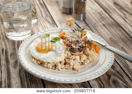 Plate with oatmeal, fried egg and vegetables on table