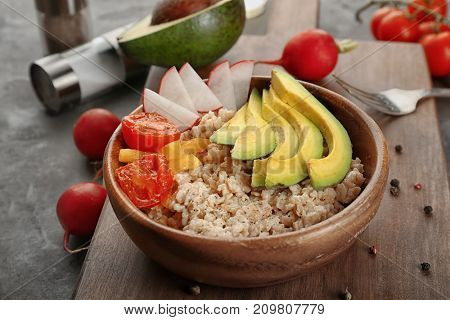 Bowl with oatmeal and fresh vegetables on table