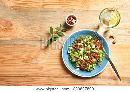 Plate with delicious goji berry salad on wooden background
