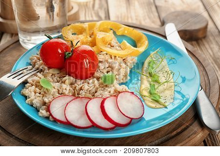 Plate with oatmeal and vegetables on table