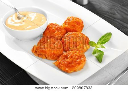 Plate with tasty sausage balls and sauce on table, closeup