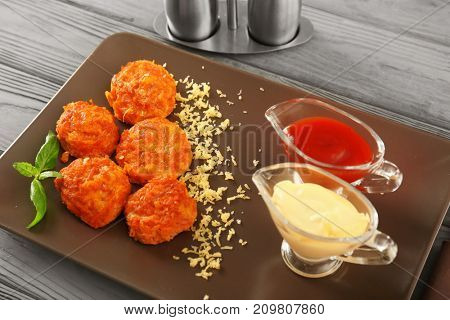 Plate with tasty sausage balls and sauces on table