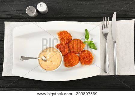 Plate with tasty sausage balls and sauce on table