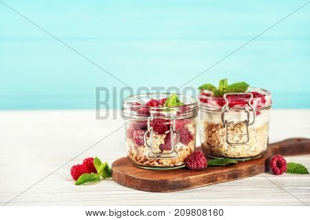 Jars with oat flakes and fresh berries on wooden background