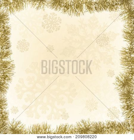 gold frame from tinsel on snowflake background