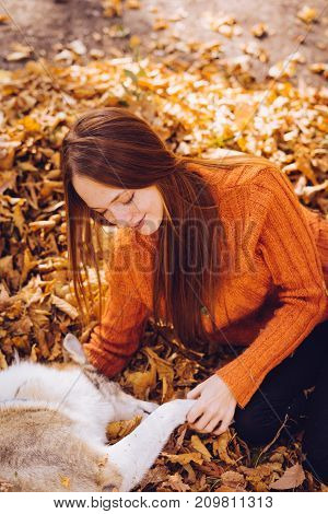 girl sitting on autumn foliage resting with her dog