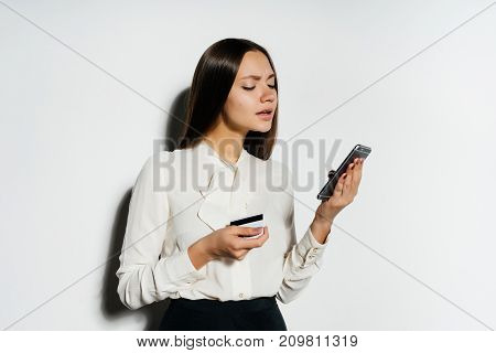 a girl with a plastic card in her hands looks at her phone sadly