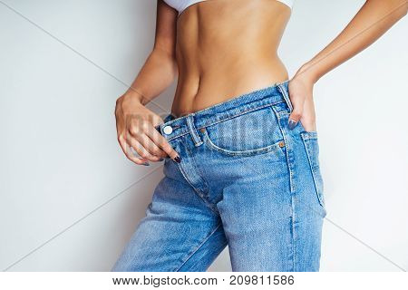 girl on white background enjoys the size of her waist