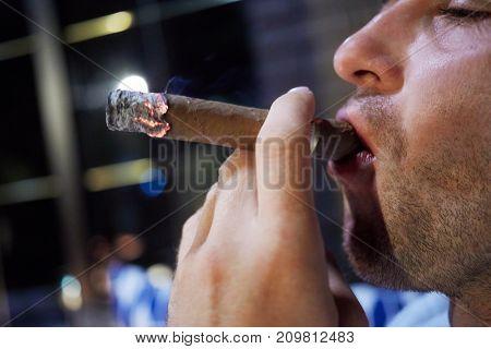 Face in profile of man smoking cigar.