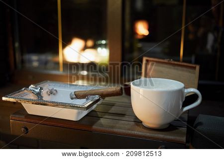 White cup of coffee, burning cigar on ashtray on wooden cigar table on veranda in evening.