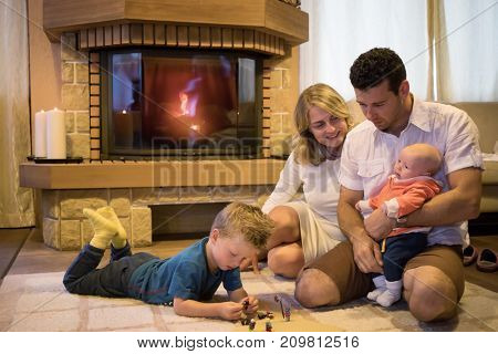 Mother. father and two sons on carpet in front of fireplace with burning firewoods in room.