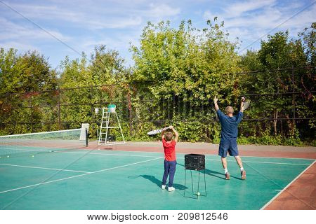 Trainer and learner play tennis on court among trees.