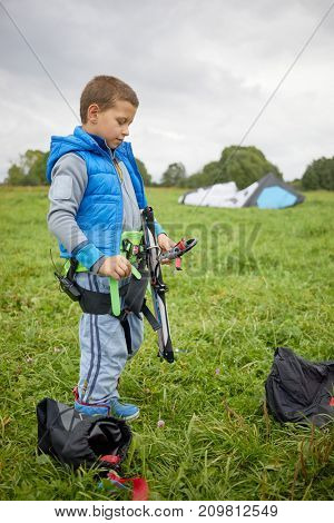 Little boy equipped for kitesurfing stands on green meadow.