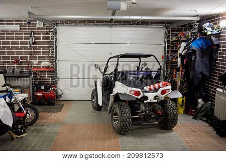 Buggy car, motorcycle, different equipment, dress and footwear inside garage room.