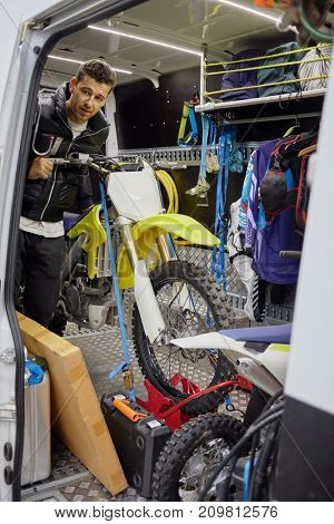 Man looks out from minivan with two motorbikes and special suits and equipment for motorbike sports.