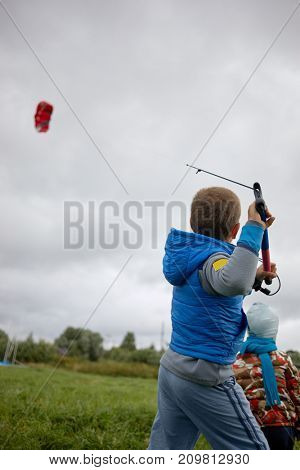 Boy learns to control power kite for kitesurfing on green meadow.