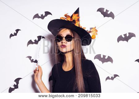 girl in a halloween costume holds a magic wand