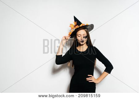 girl in a witch suit wearing a hat on a white background