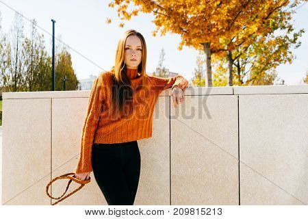 girl posing against the background of autumn trees