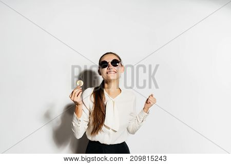 a girl in black glasses is holding a couple of bitcoins in her hands