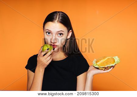 girl eating an apple instead of a burger in the other hand