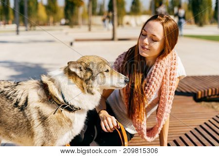 the girl is sitting in the park on the bench with her dog