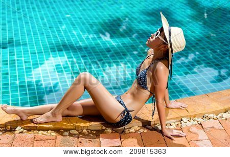 Bikini young asian woman sexy in pool relaxing young asian beautiful female resting in vacation on summer season with hat at resort swimming pool edge