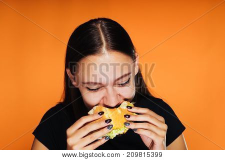 happy girl bites into a burger on an orange background