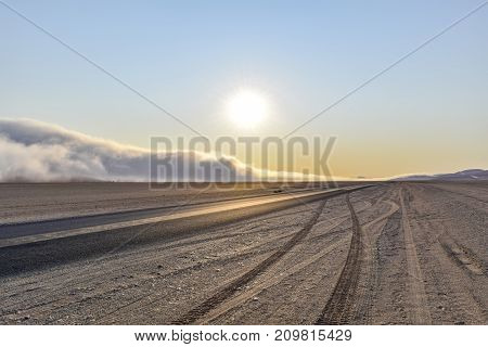 abandoned area with dusty dirt road and some fog at evening time in Namibia Africa