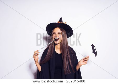 a girl in a witch suit makes a cunning expression
