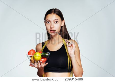 the girl looks thoughtfully forward holding a bowl of vegetables and apple in hands