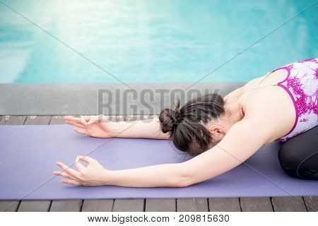 Beautiful young Asian happy woman doing yoga exercise near swimming pool. Healthy lifestyle and good wellness concepts